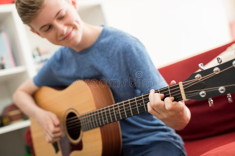 Tienerzitting op Sofa At Home Playing Guitar stock afbeeldingen