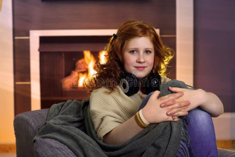 Tienerzitting thuis bij open haard royalty-vrije stock fotografie