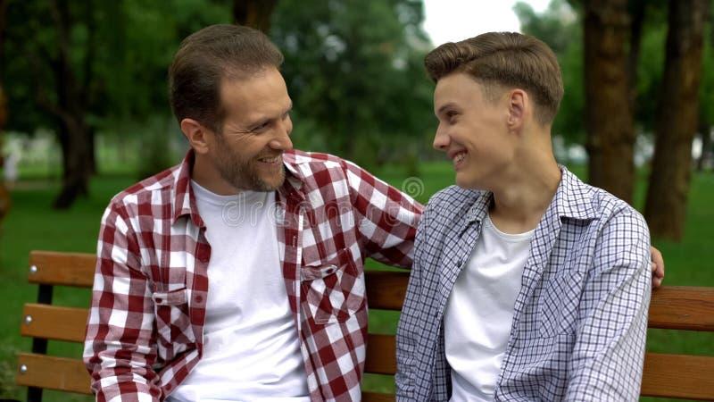 Tienerzoon die met vader op bank, het vertellen geheimen spreken en het glimlachen, vertrouwen stock fotografie