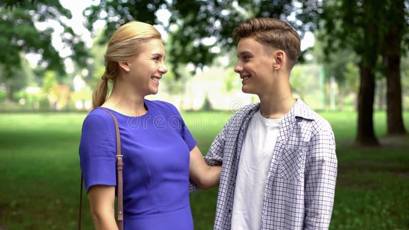 Tienerzoon die zijn geliefde moeder, vriendschappelijke verhoudingen, begrip kussen royalty-vrije stock foto's