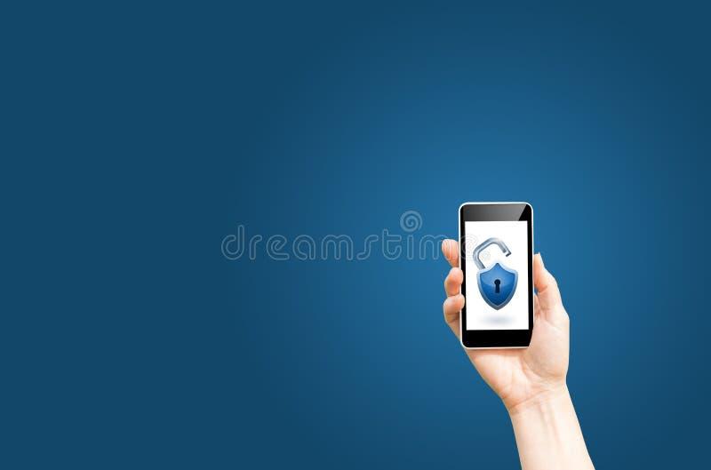 Tient le téléphone intelligent avec la serrure ouverte sur un fond bleu photo libre de droits