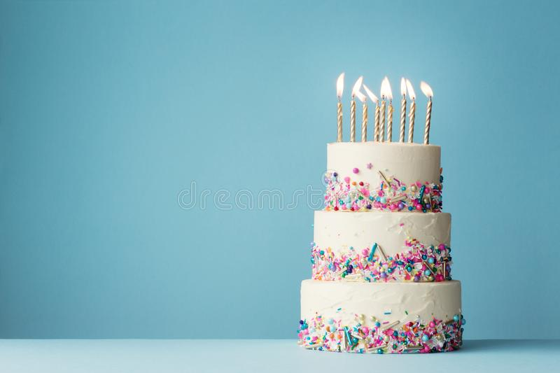 Tiered birthday cake with sprinkles. Birthday cake with three tiers and colorful sprinkles royalty free stock photos