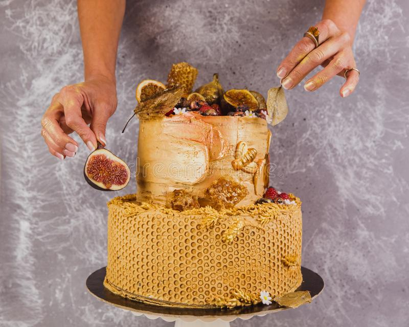 Tiered cake decorated in an autumn theme in gold color. With honeycomb and figs royalty free stock photo