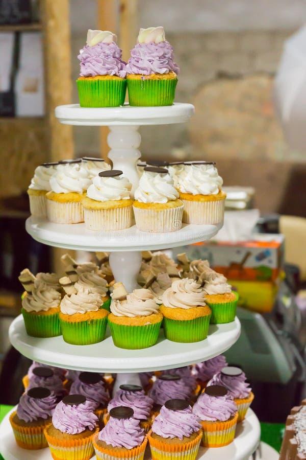 Tiered kakaställning med färgrika muffin royaltyfri foto