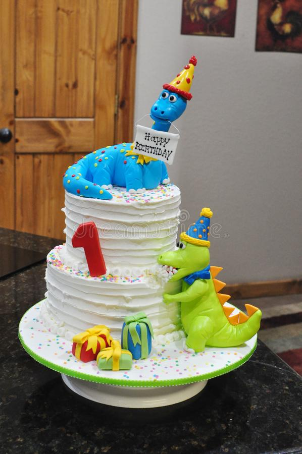 Child`s Dinosaur Birthday Cake. 2 tiered kids birthday cake with edible fondant dinosaurs.  Buttercream finish with bright colored toppers stock photo
