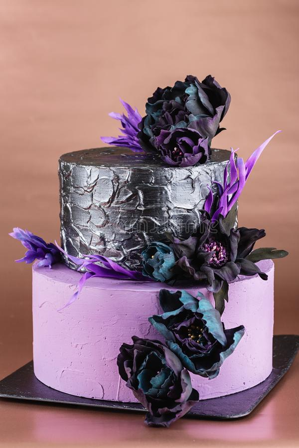 Tiered wedding cake with black fake flowers royalty free stock photos