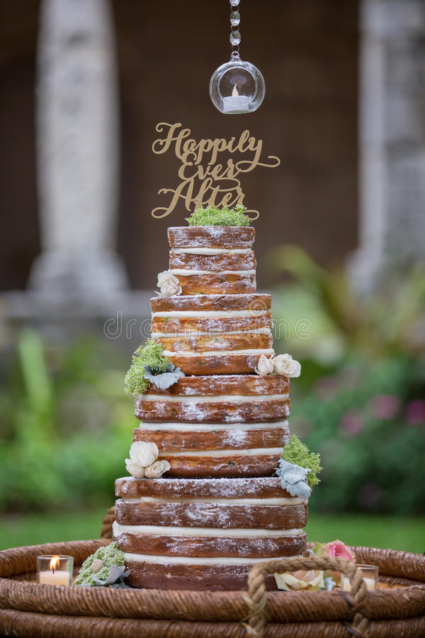 Tiered wedding cake. Vintage wedding cake without frosting decorated with candles and flowers royalty free stock image