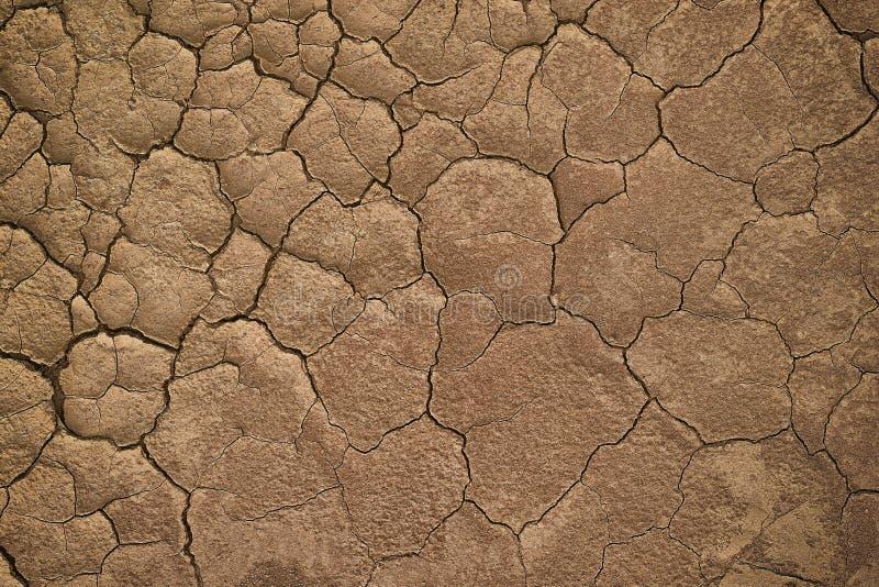 Tierra agrietada seca durante en una estación de lluvias porque falta de escasez de la lluvia de textura agrietada del suelo del  fotos de archivo libres de regalías