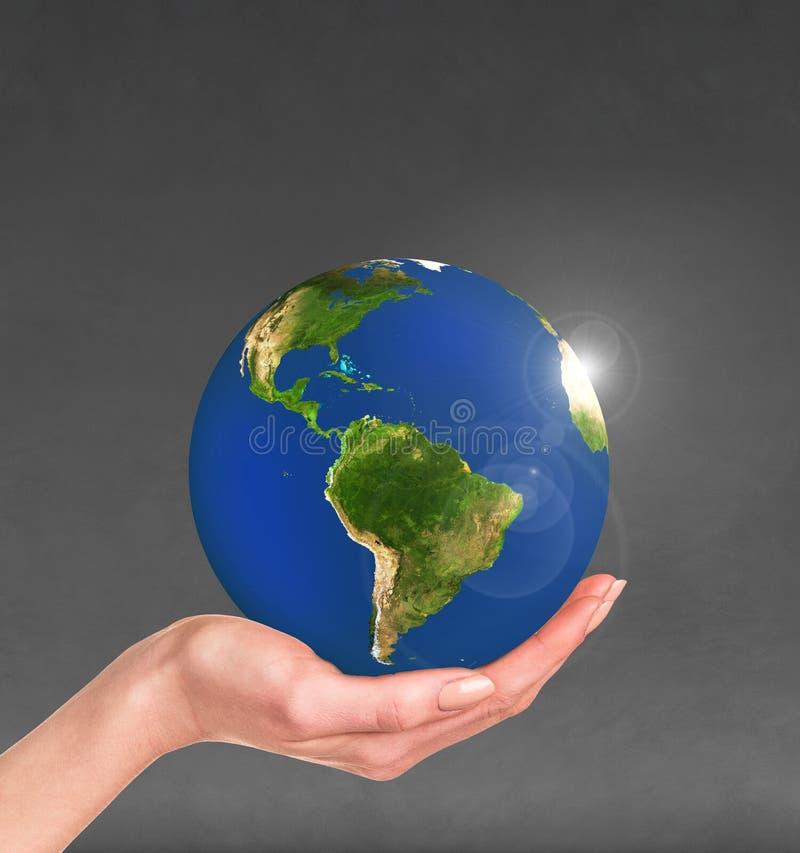 Tierra del planeta en una mano humana stock de ilustración
