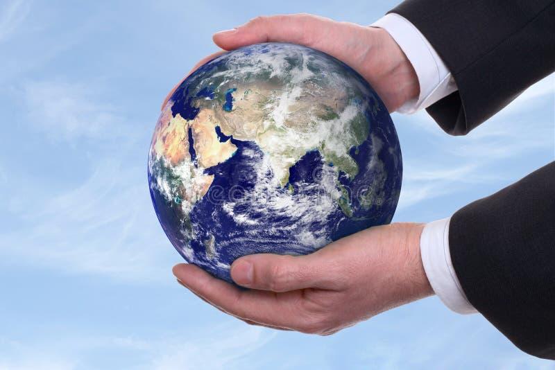 Tierra en manos, azules imagen de archivo libre de regalías