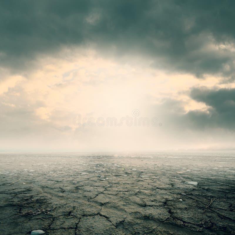Tierra erosionada seca agrietada y cielo nublado imagen de archivo