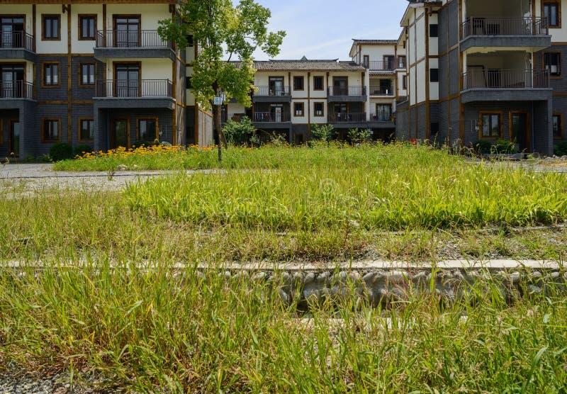 Tierra guijarro-pavimentada herbosa antes del edificio de la vivienda del campo imagen de archivo libre de regalías