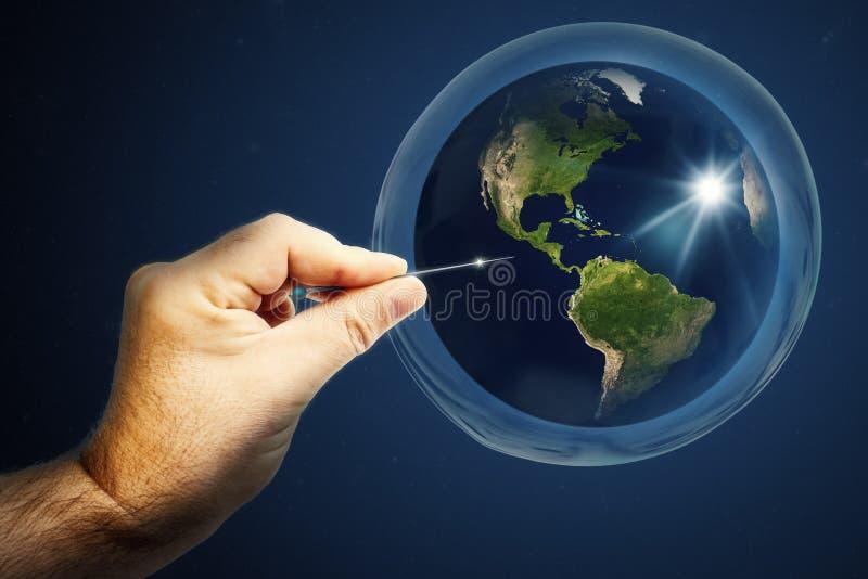 Tierra planetaria en una burbuja de jabón y una mano con una aguja que reventó todo imagenes de archivo