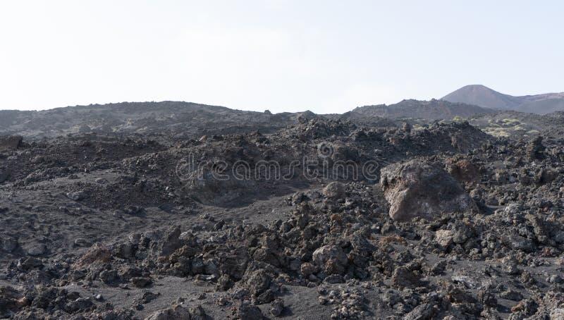 Tierras rocosas volcánicas con desierto árido negro en Isla Canaria Suelo de lava y basalto en un parque nacional imágenes de archivo libres de regalías