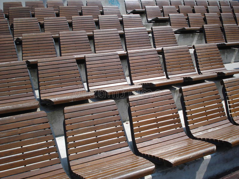 Tiers of wooden chairs in outdoor arena. Tiers of wooden armless fixed chairs in outdoor sports arena royalty free stock photos