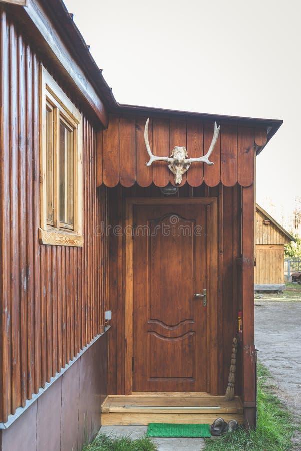 Tierschädel über dem Eingang zum Holzhaus Die Geweihe des Hirsches gegen wei?en Hintergrund lizenzfreie stockfotos