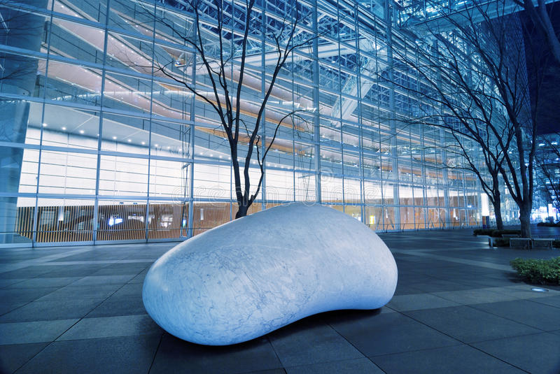 TIF, Tokyo. Big white stone and scenic trees alley under illuminated wall inside famous Tokyo International Forum exhibition Trade Center area, Japan royalty free stock photo