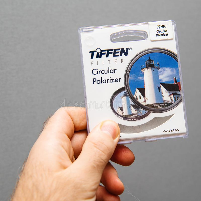 Tiffen Circular Polarizer filter for 77mm diameter camera lens. Paris, France - Jan 3, 2018: Man hand holding against gray background professional Tiffen stock photography