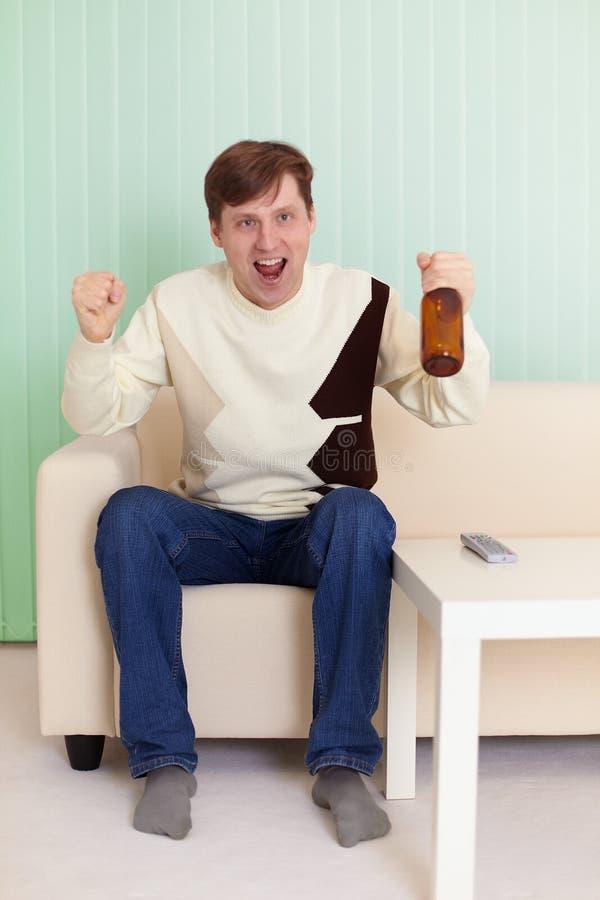 Tifoso che si siede sul sofà con la TV fotografie stock