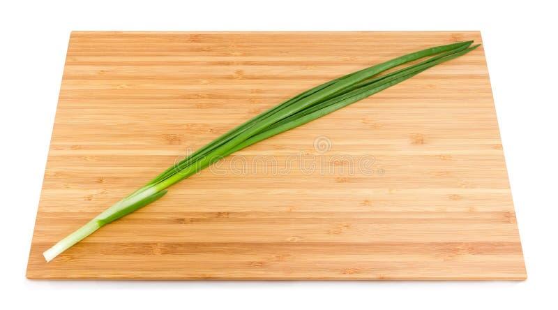 Tige d'oignon vert sur la planche à découper en bambou images stock
