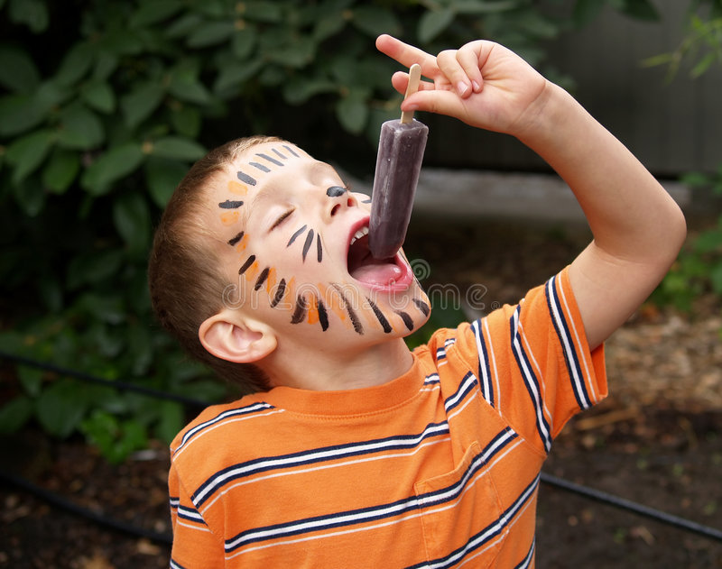 Tiger boy eating popcicle royalty free stock images