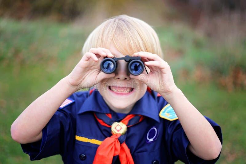 Tiger Cub Scout Smiling giovane alla macchina fotografica tramite il binocolo immagine stock libera da diritti
