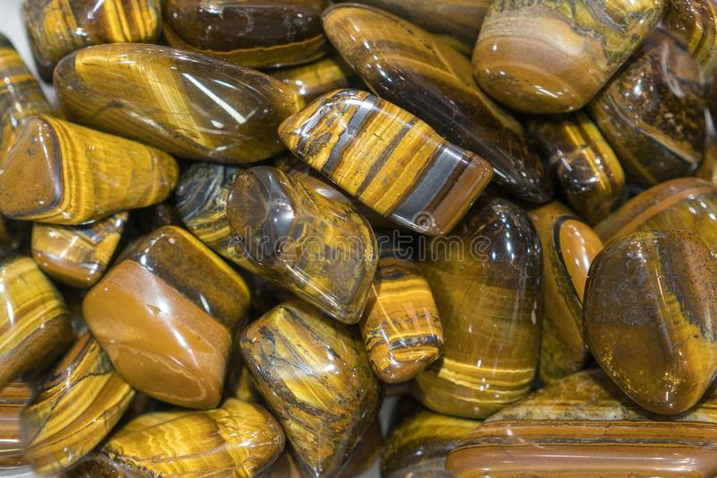 Tiger Eye Stones Ready to Make Handmade Jewelry. tiger`s eye and hawk`s eye gemstone as natural mineral rock specimen.  royalty free stock images