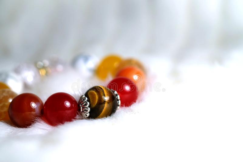 Tiger eye and various quartz lucky stone bracelet in red and white tone on white wool texture background stock photography