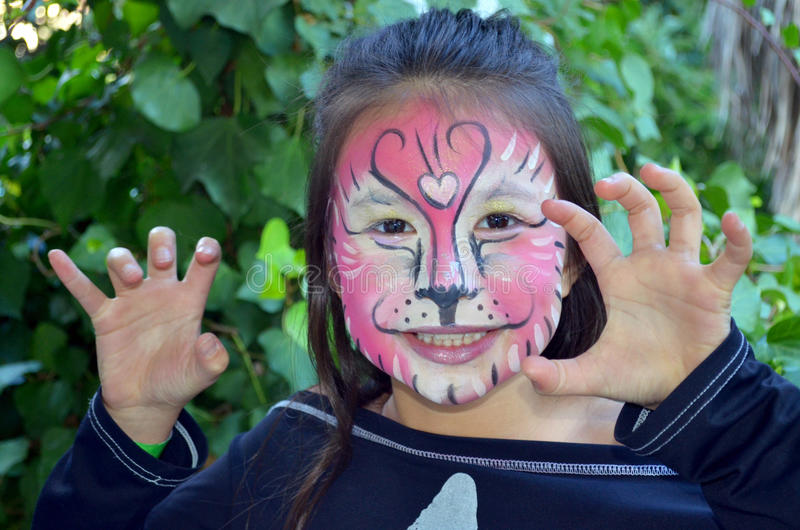 Tiger face painting. Little girl having fun after having a tiger face painted royalty free stock photo