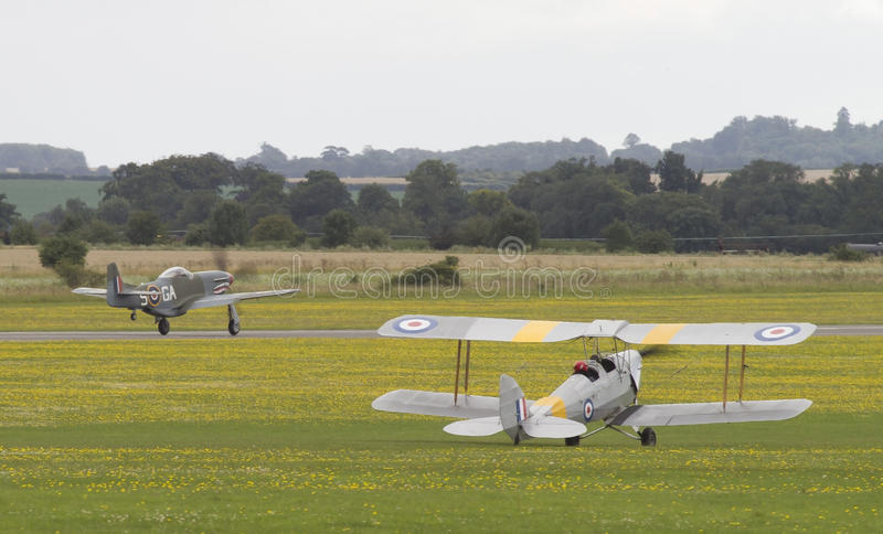 Tiger Moth biplane with P51 Mustang on takeoff. stock photography
