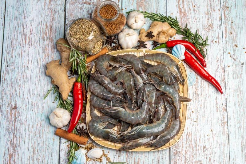 Tiger Prawns fresco em uma placa do rattan cercou por ingredientes crus frescos foto de stock royalty free