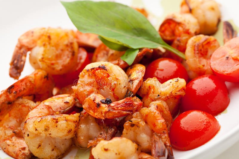 Tiger Shrimps. Appetizers - Fried Tiger Shrimps with Garlic and Cherry Tomato stock images