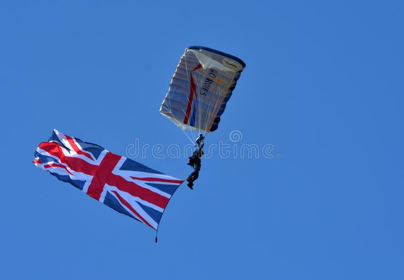 The Tigers Army Parachute Display Team flying large Union Flag against blue sky. LITTLE  GRANSDEN,  CAMBRIDGESHIRE, ENGLAND - AUGUST 25, 2019:  The Tigers Army stock image