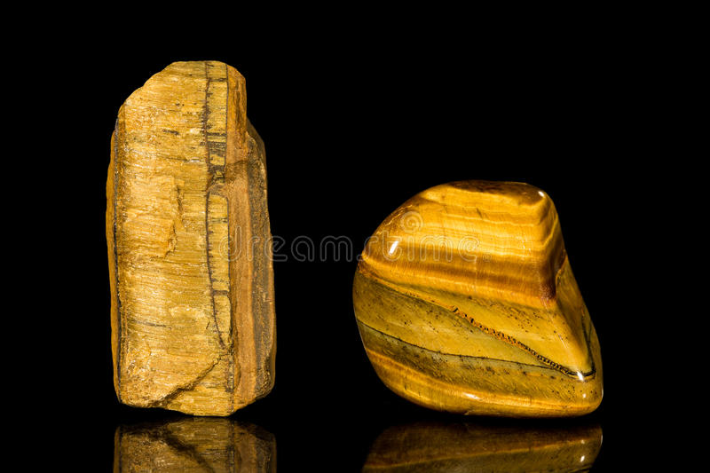 Tigers-eye, uncut and Tumble finishing. With black background and reflection stock photography