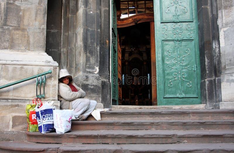 Tiggarekvinna som sitter på tröskeln arkivfoton