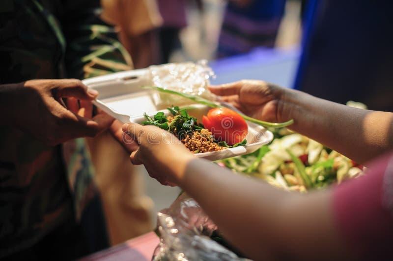 Tiggaren tigger mat fr?n givare: Att bry sig f?r med- m?nniskor i samh?lle, genom att ge mat som ger sig utan hopp: Begreppet av  fotografering för bildbyråer