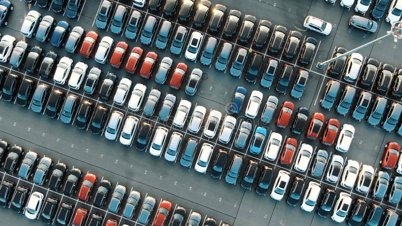Tight coloured car rows on parking area vertical upper view. Tight coloured finished car rows on warehouse parking area with modern lighting on sunny summer day royalty free stock photography