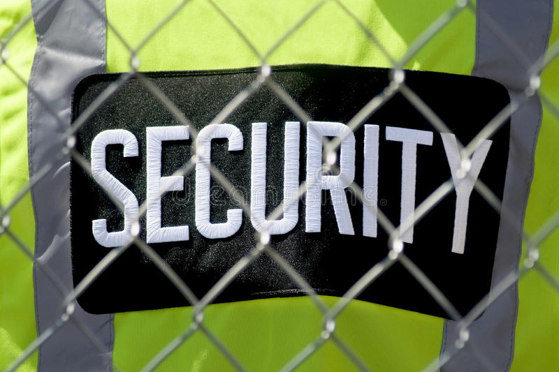 Tight Security. Security guard's lime green vest behind a fence royalty free stock photos