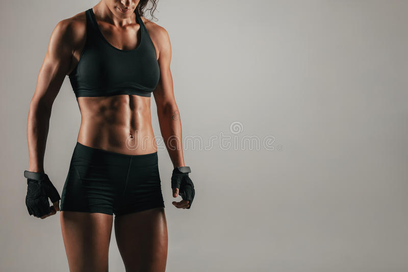 Tight view of woman with strong abdominal muscles. Tight view of woman in black weight lifting gloves with strong abdominal muscles over gray background with royalty free stock photo