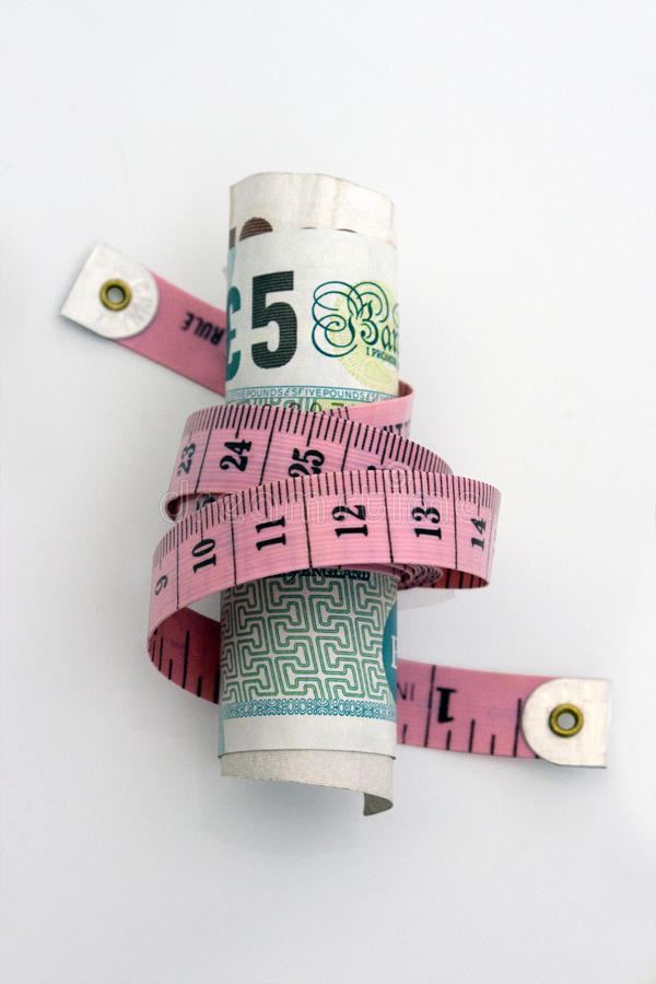 Tighten Budget. £5 and £10 note wrapped tightly by a measuring tape. The photo conveys concepts such as, inflation, budget reduction, cost cutting and money stock image