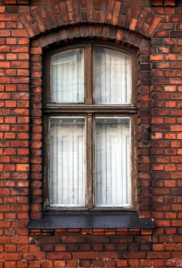 Tightly closed wooden window in red brick wall of old residential building front view close-up stock photos