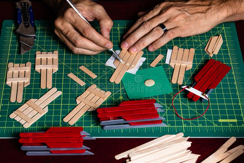 A tightly framed shot of someone working on crafts for the Christmas season.  Only the craftsman's hands are visible in the shot. While he glues and cuts royalty free stock image