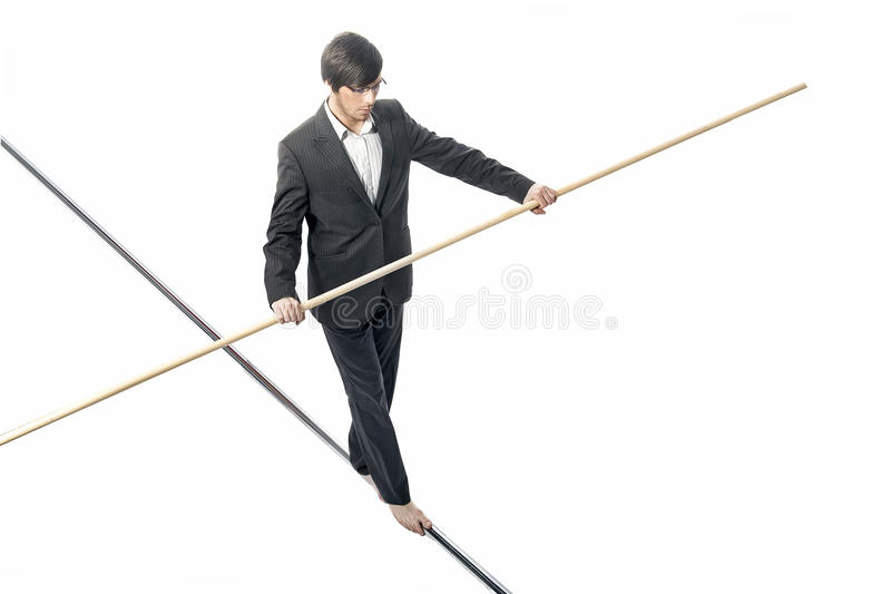 Tightrope. Businessman walking a tightrope - isolated on white