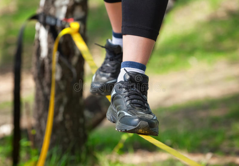 Tightrope walker is on a tight sling, which is fixed on the trees, at a low altitude. stock image