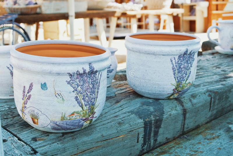TIHANY, HUNGARY - AUGUST 05, 2017: Bright white textured hand-made pots with hand-painted bouquets of lavender and butterflies on royalty free stock photography