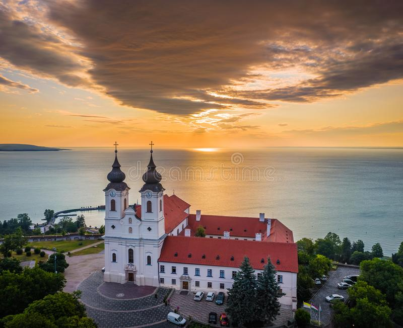 Tihany Ungern - flyg- surrsikt av den berömda Benedictine kloster av den Tihany Tihany abbotskloster med dramatisk guld- himmel royaltyfri foto