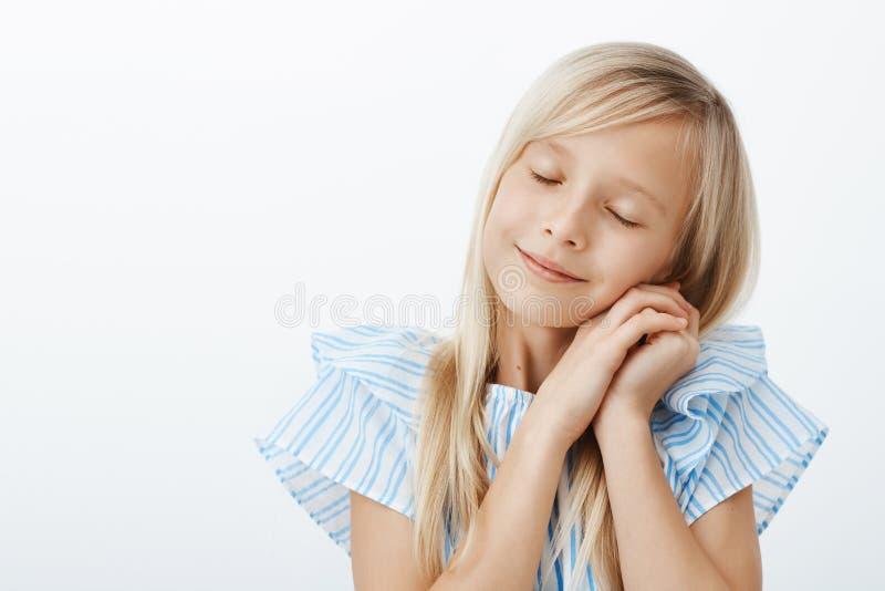 Tijd aan slaap Slaperige leuk weinig Europees meisje met blond haar, sluitende ogen en het leunen op palmen alsof slapend royalty-vrije stock afbeeldingen