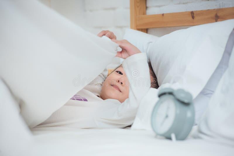 Tijd aan slaapconcept Kind in slaapkamer met stiltegebaar meisje met gelukkige gezicht het spelen deken op bed met wekker, tijd royalty-vrije stock foto's