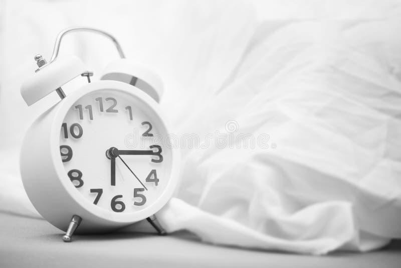 Tijd achtergrondconcept Wekker op bed, kielzog omhoog in morn stock foto's