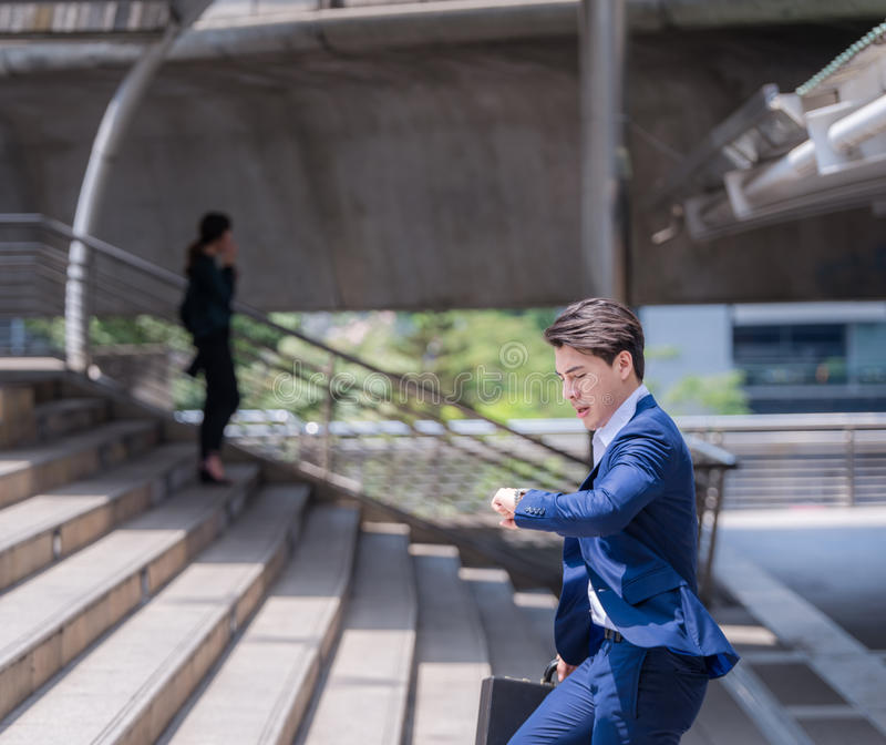 Tijd controleren en zakenman die in zeven haasten, is hij laat voor het werk zijn bedrijfsbenoeming lopen stock foto